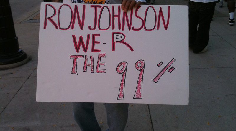 """A protestor holds a sign reading """"Ron Johnson R are the 99%"""""""